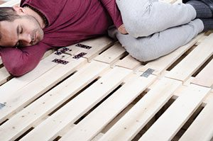 Man Sleeping On Firm Wooden Pallets