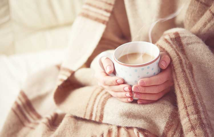 Comforted under a weighted blanket with hot chocolate
