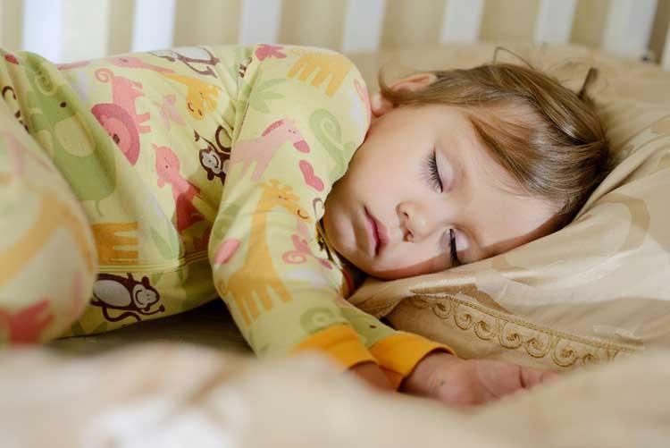 Little girl sleeping in cot bed duvet