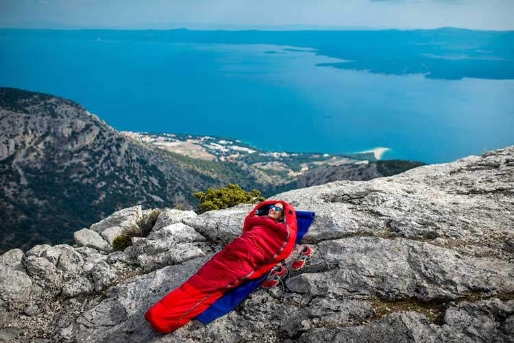 Man In Sleeping bag on Cliff