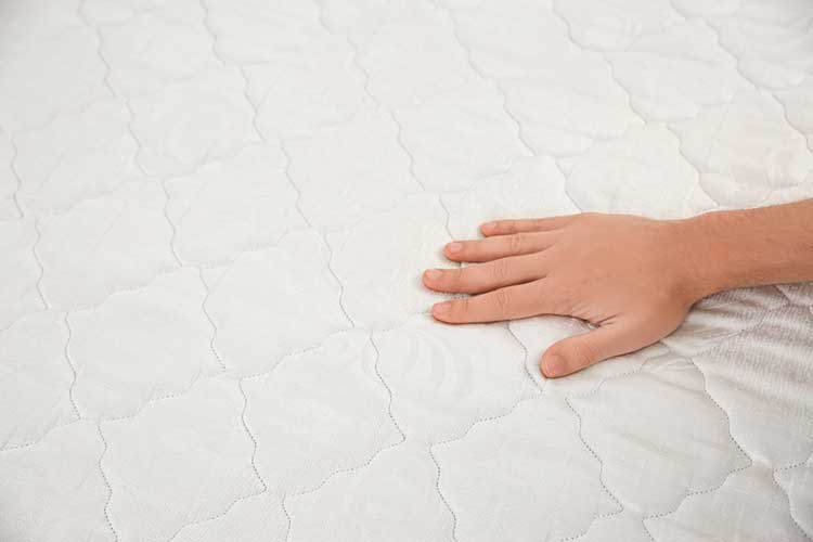 Man CHecking mattress firmness